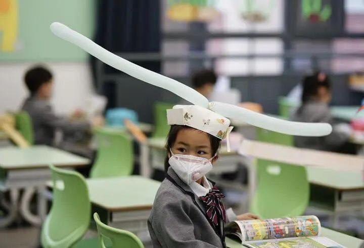 Școlarii din China cu pălării de distanțare socială