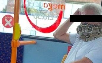 Un englez folosește un șarpe înfășurat în jurul gurii pe post de mască. Un șarpe viu
