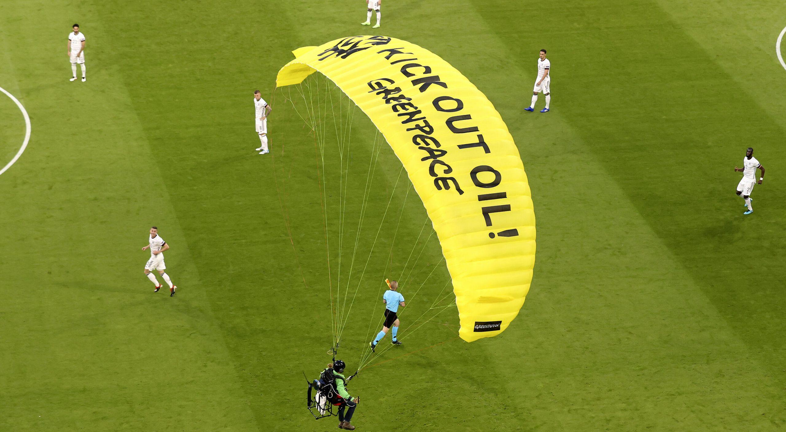 VIDEO| Activistul Greenpeace care s-a parașutat pe stadion înainte de meciul Franța – Germania a fost reținut de poliție